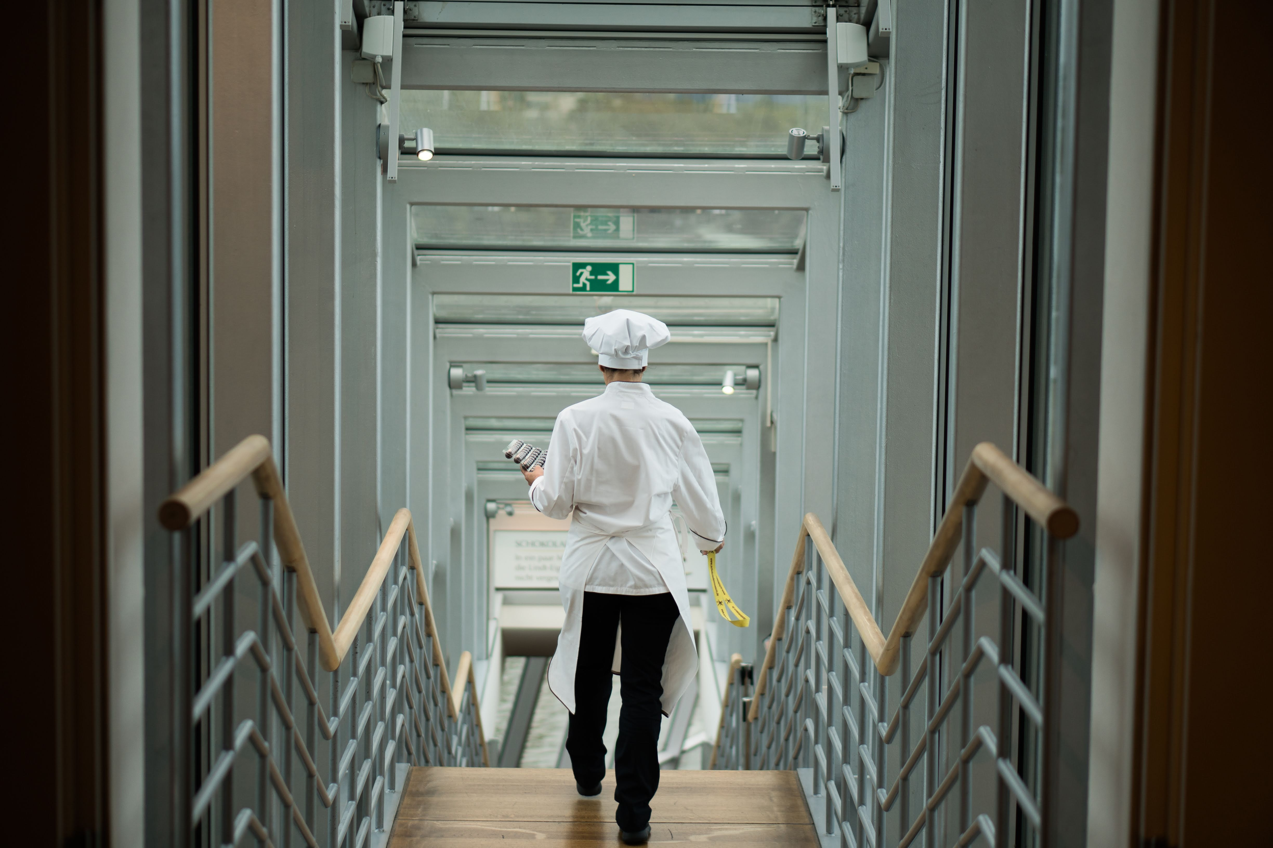 person wearing white apron walkin on stairs