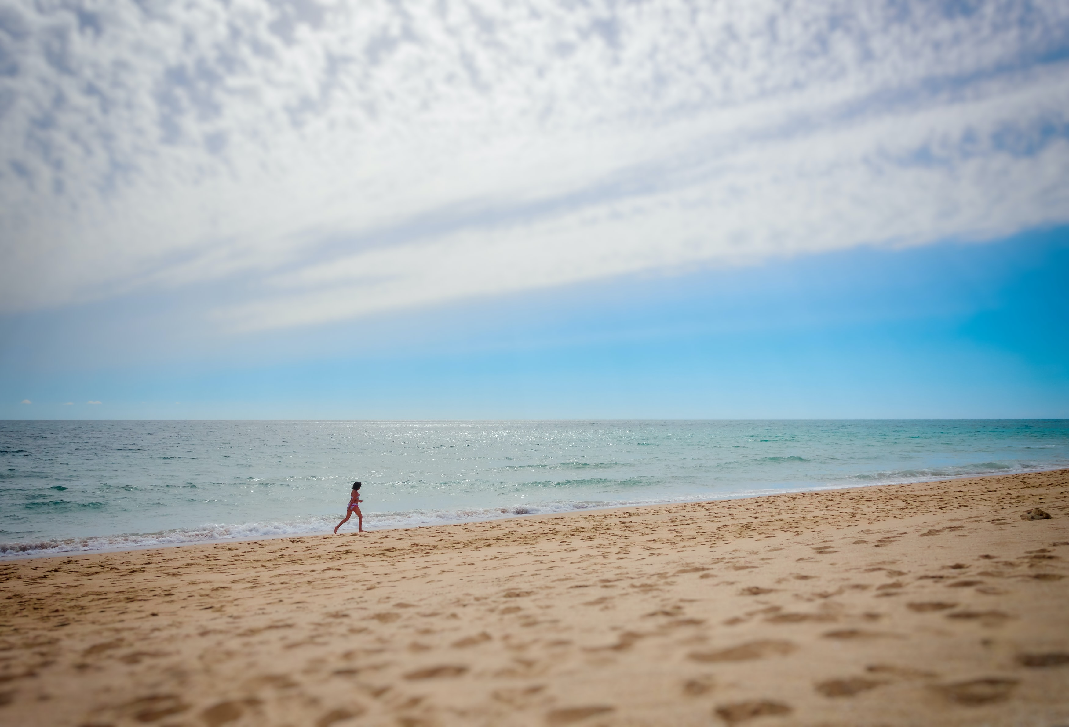 person running on beach during daytime