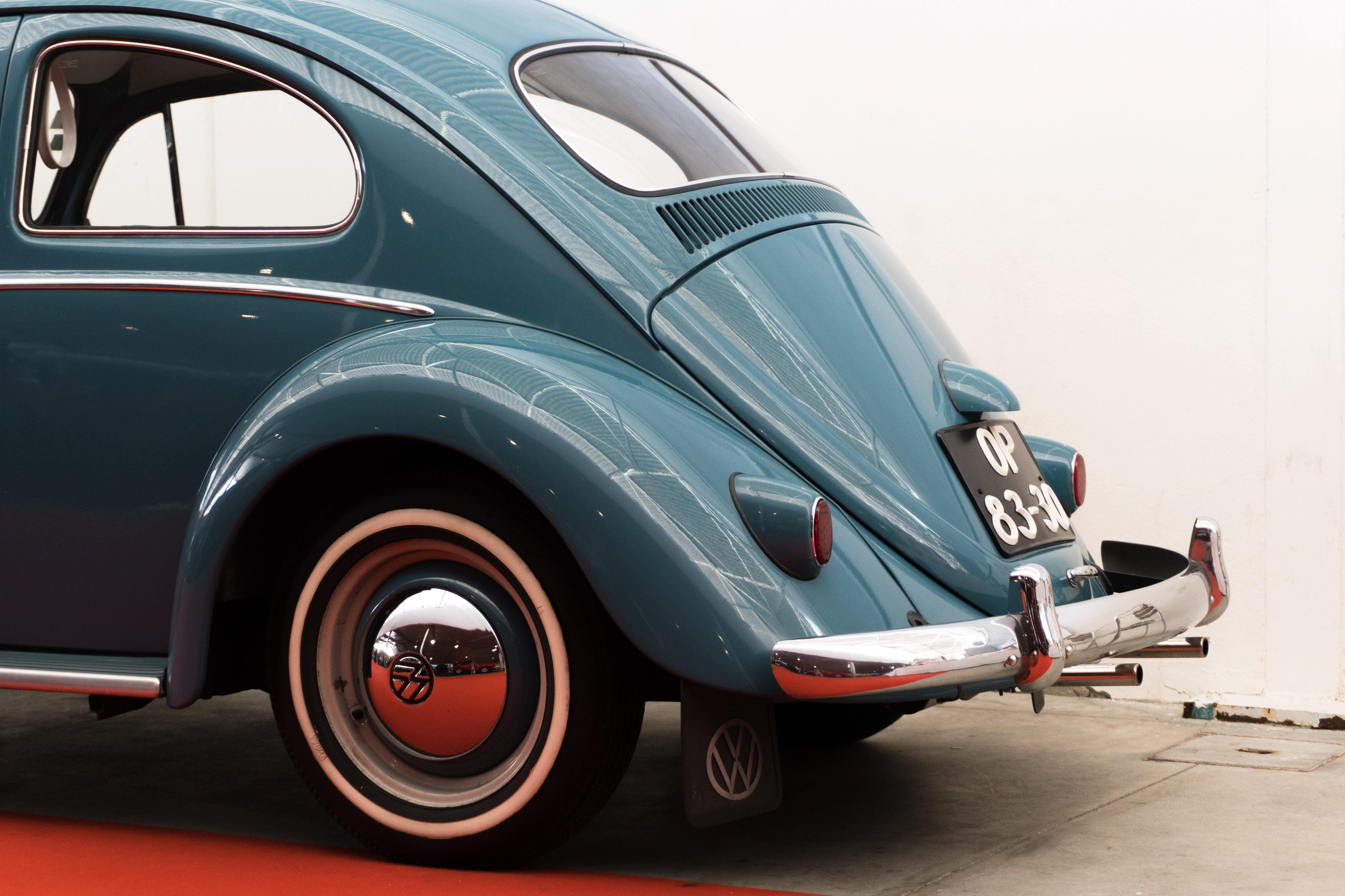 blue Volkswagen Beetle coupe parked near white wall