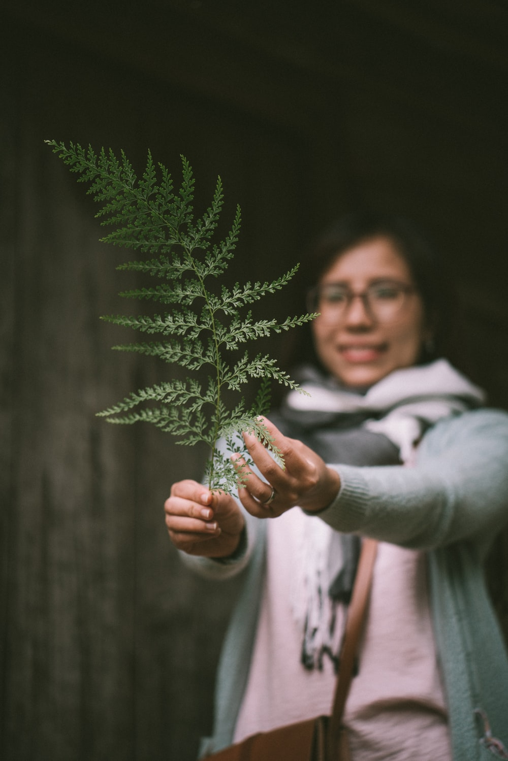 woman holding green leaf while smiling