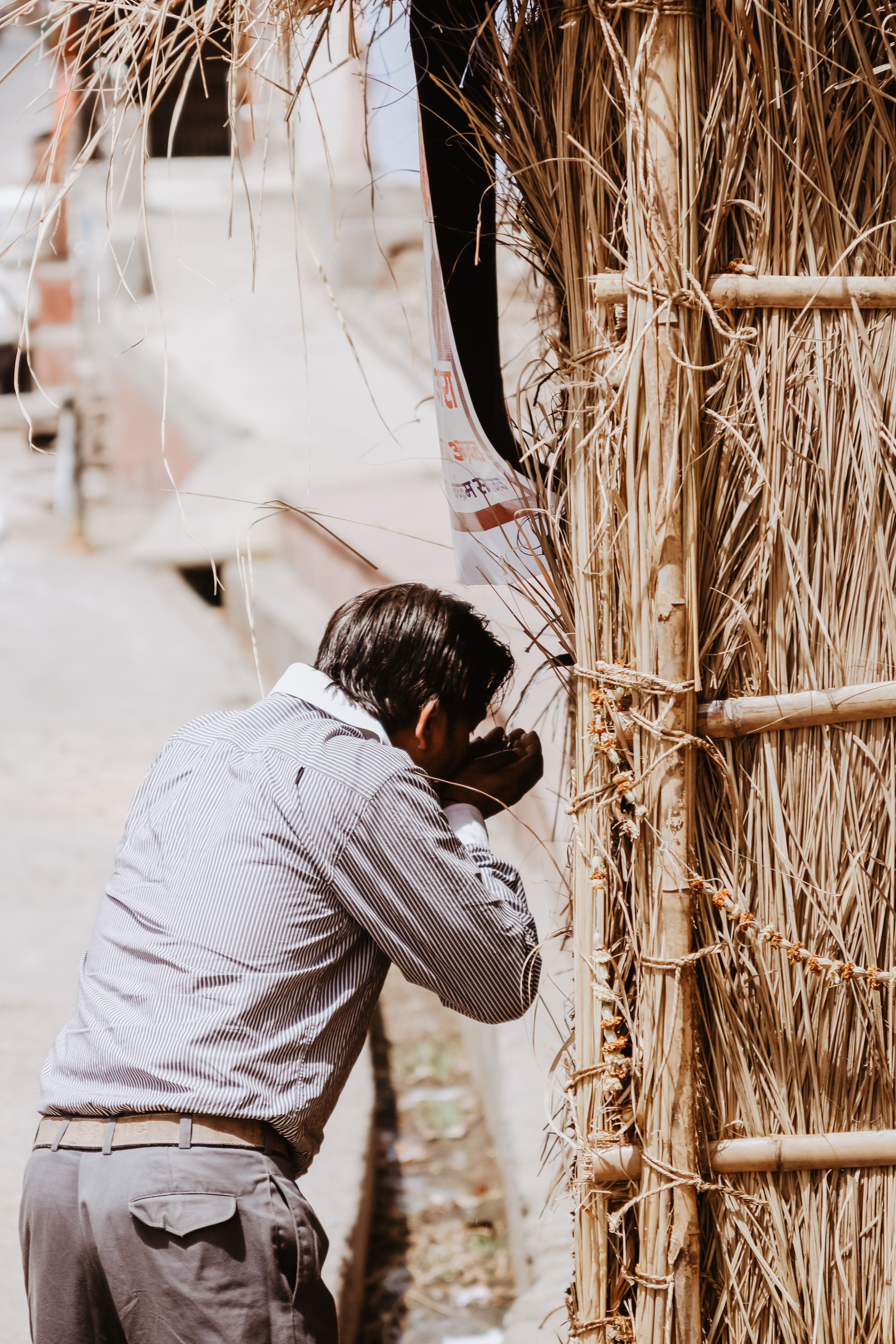 person standing near bamboo hut during daytime