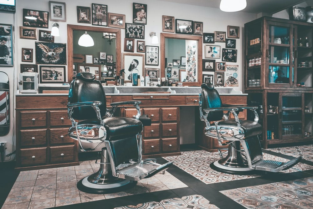 two barbers chairs in front of mirrors inside room