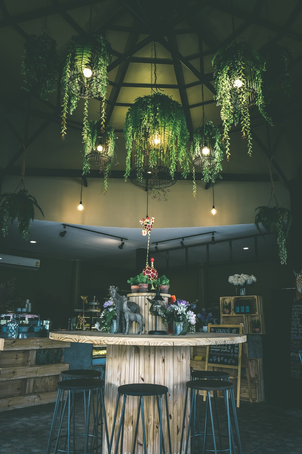 round brown wooden table surrounded by black stools under green leafed-themed pendant lamps