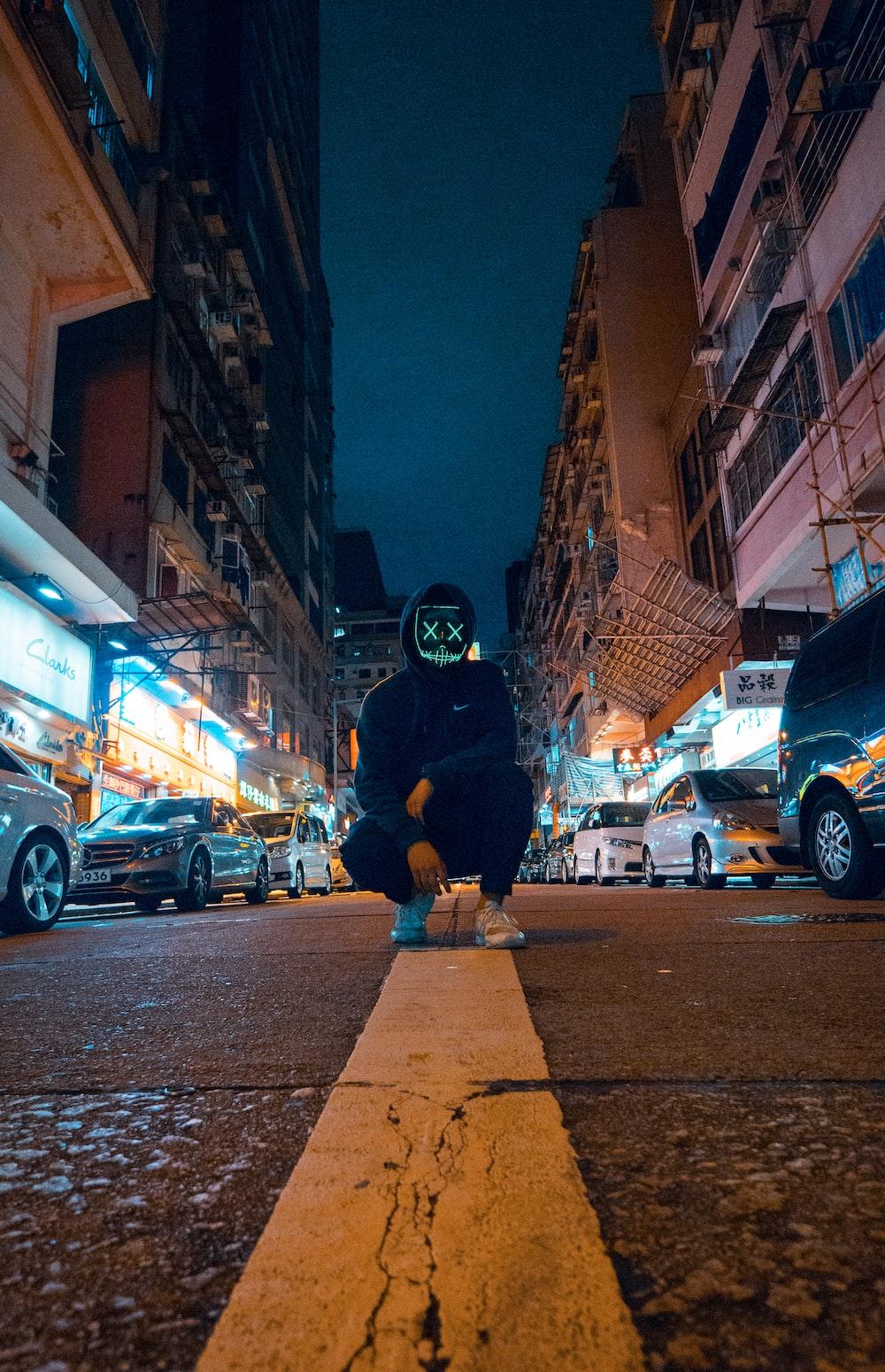 man wearing black hoodie knee on road with mask