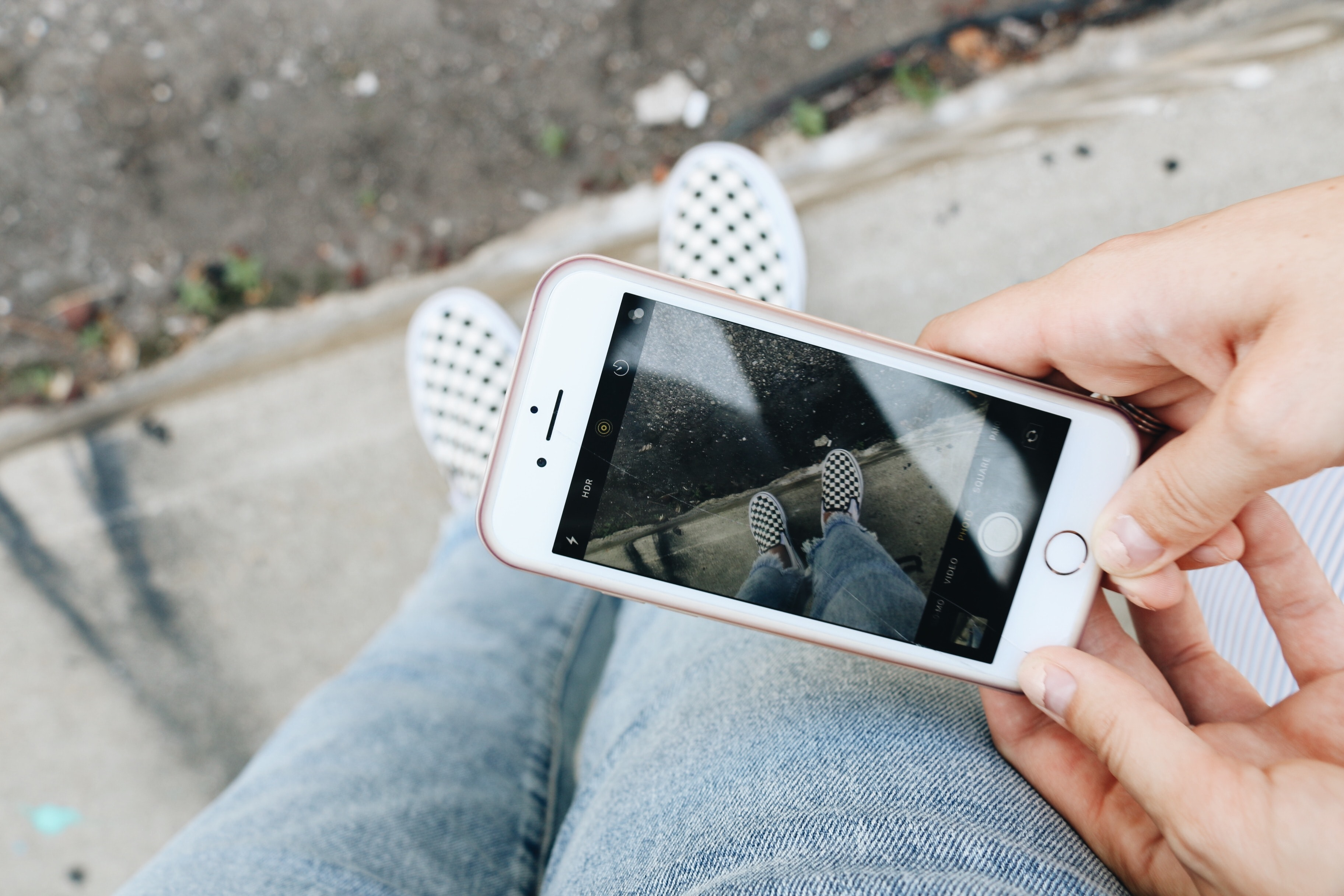 person holding rose gold iPhone 6s capturing pair of white sneakers