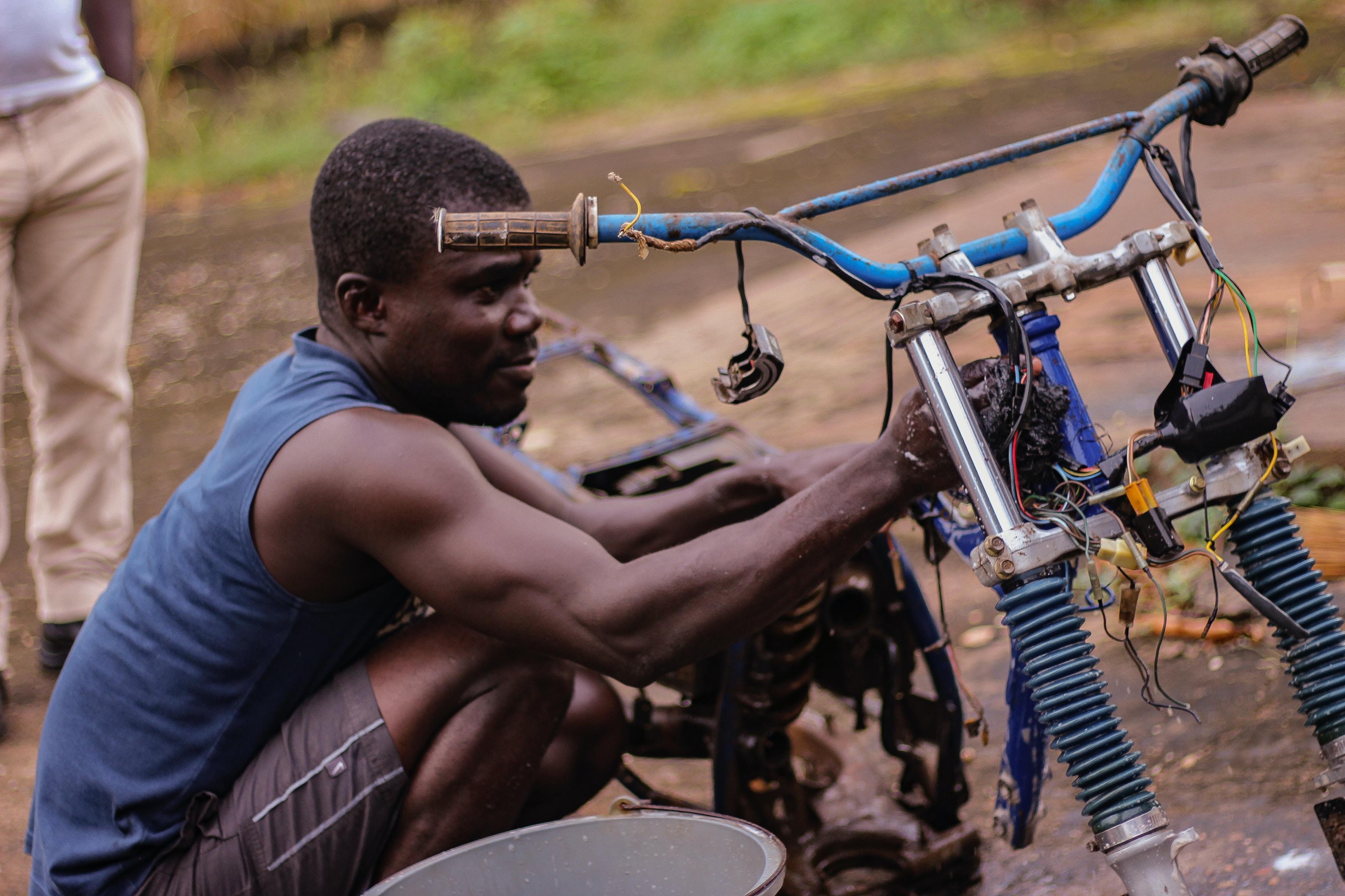 man fixing motorcycle during daytime