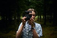 man holding a black instant camera