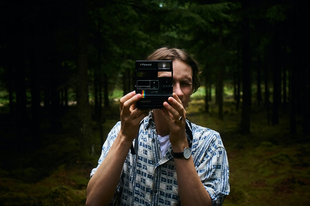 man holding a black instant camera