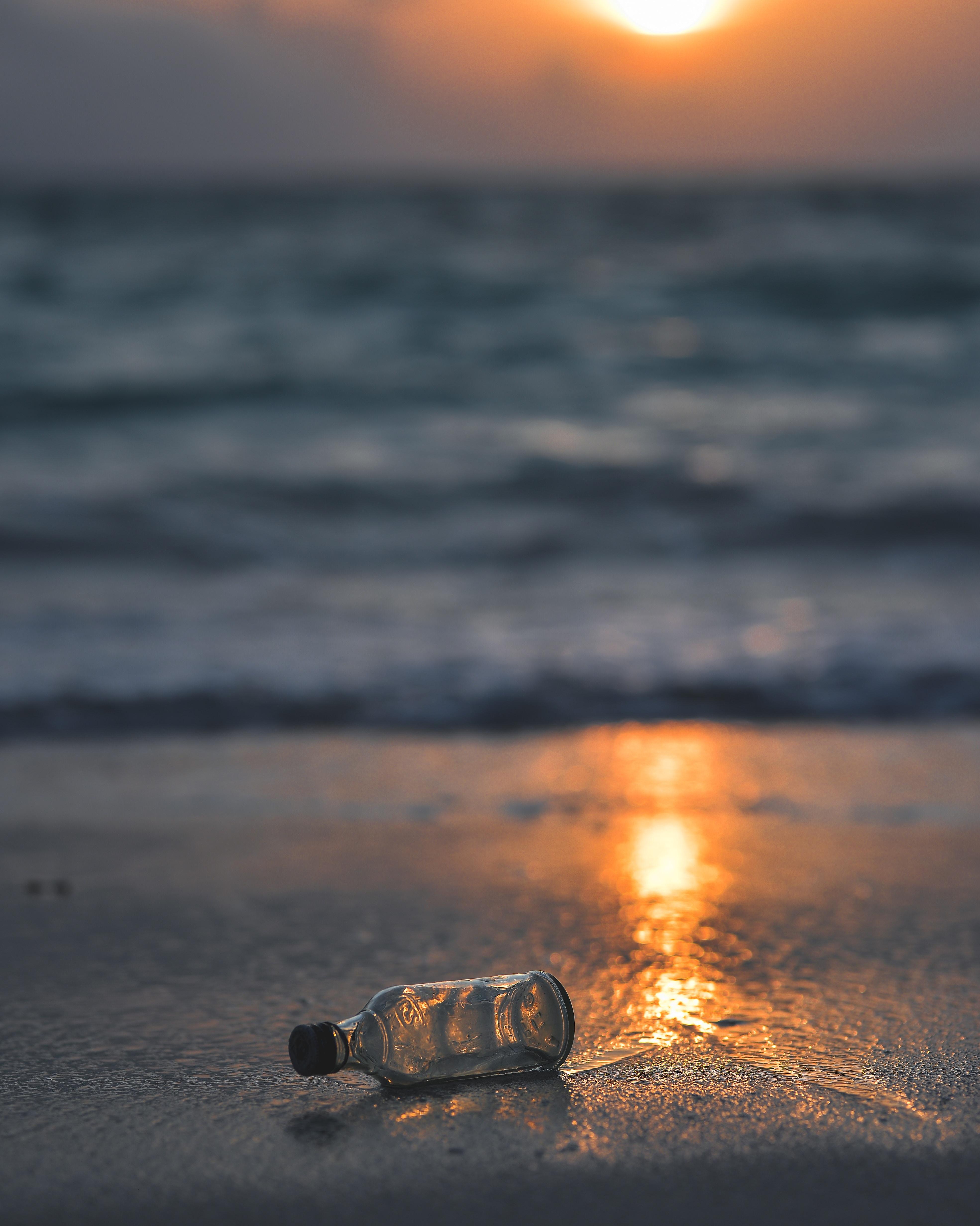 clear glass bottle on seashore