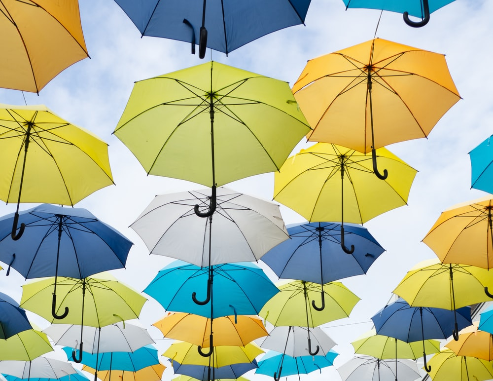 assorted-color umbrella lot under white clouds at daytime