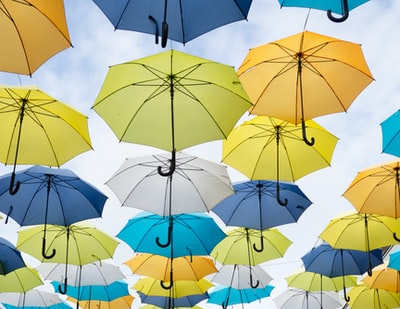 assorted-color umbrella lot under white clouds at daytime weather teams background