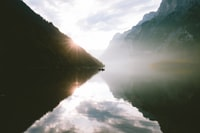 silhouette photo of mountain near lake at daytime