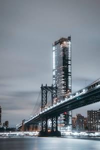 concrete bridge near high-rise building at cloudy sky