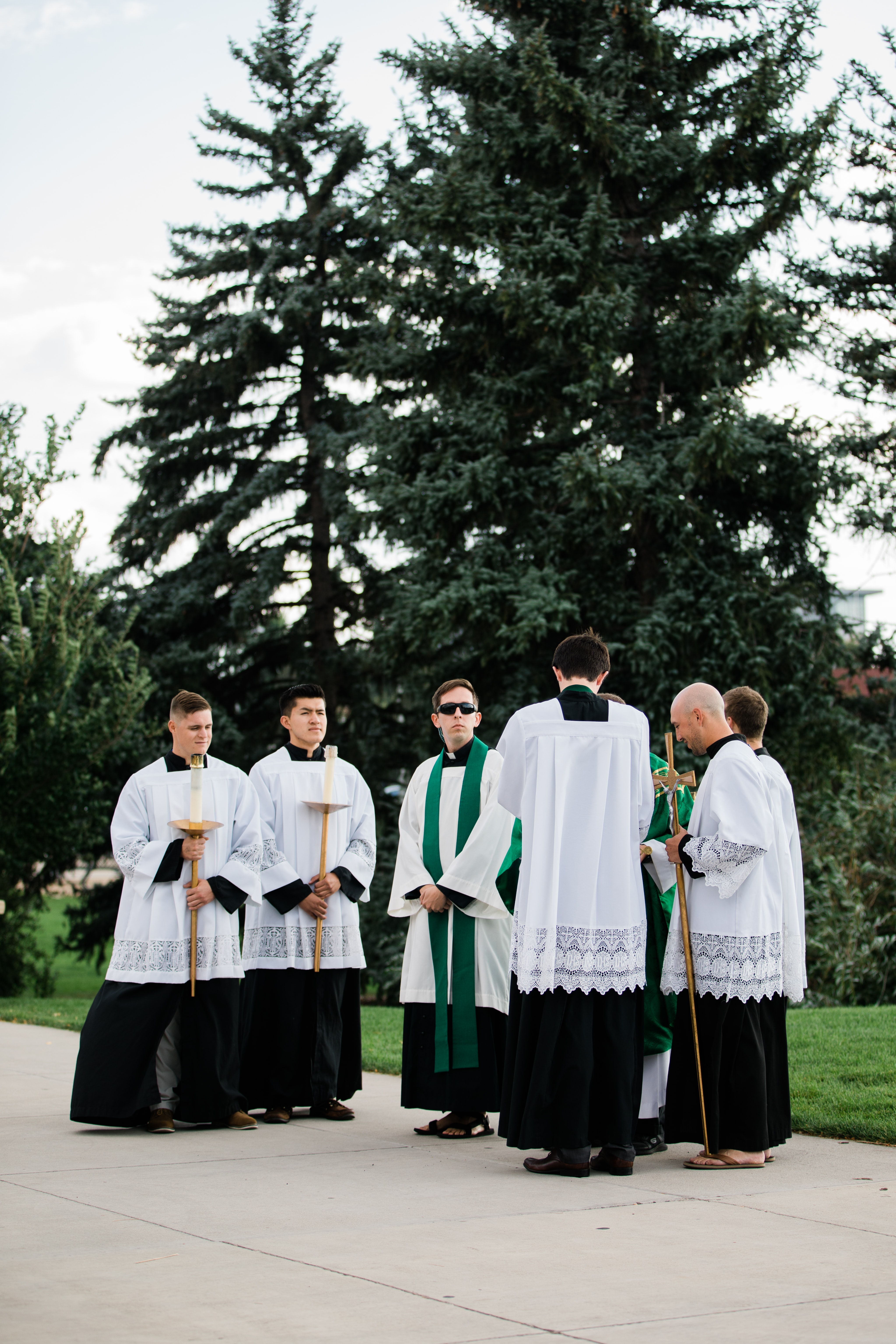 priests and altar boys standing on concreted pavement