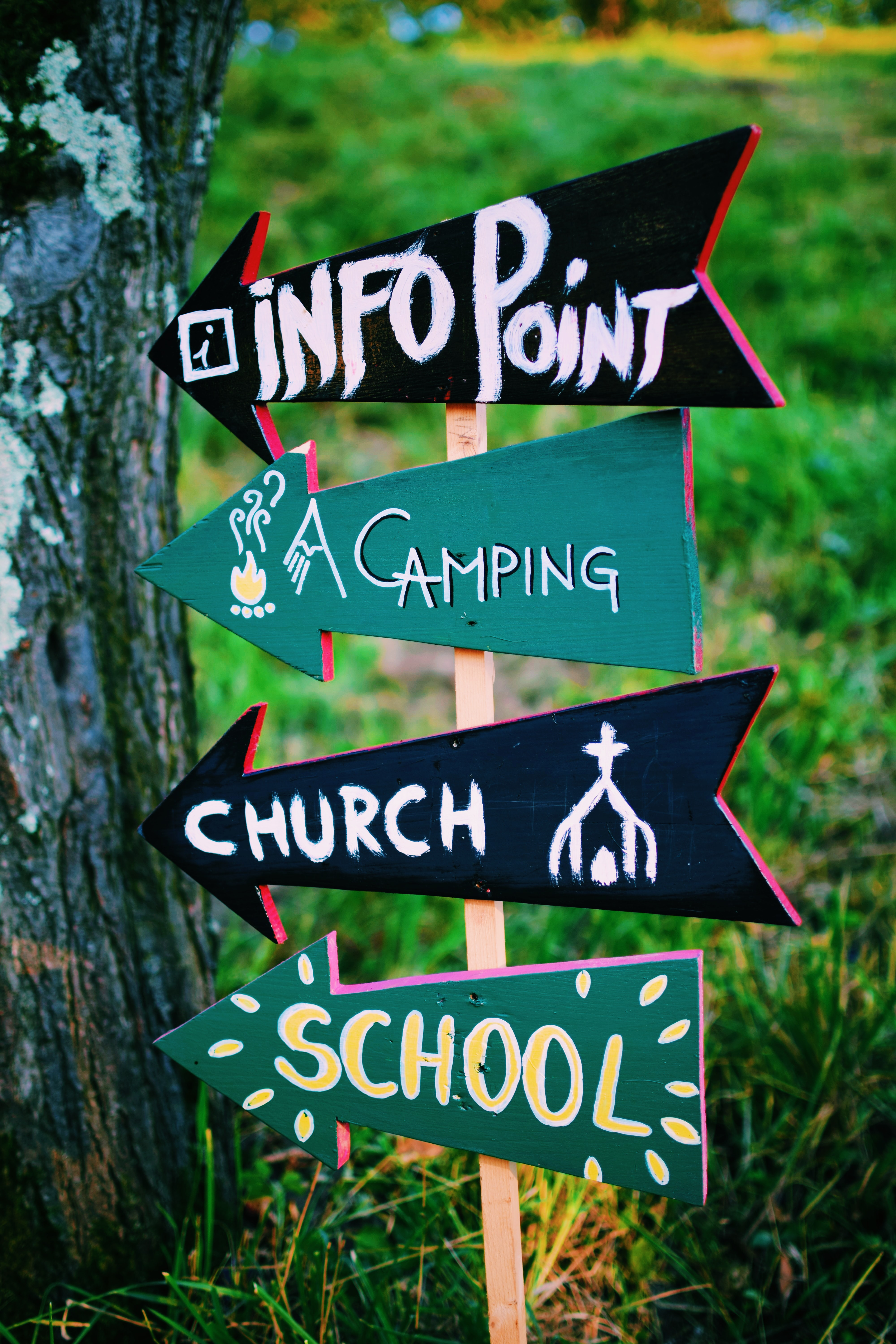 selective focus photography of Info point, camping, church and school signage on the left