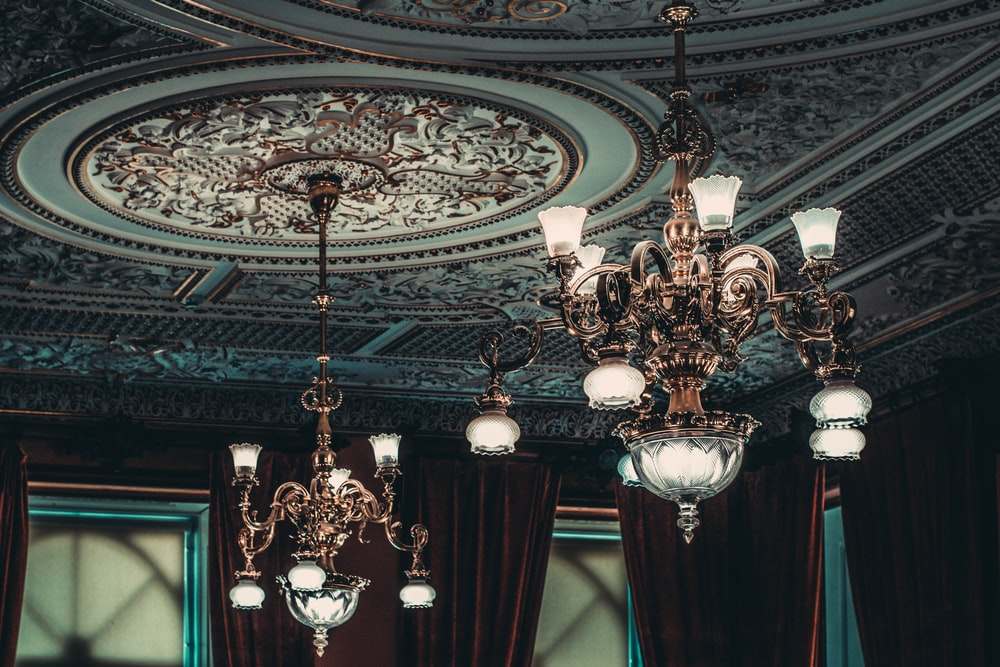 two gold-colored chandeliers on ceiling inside room