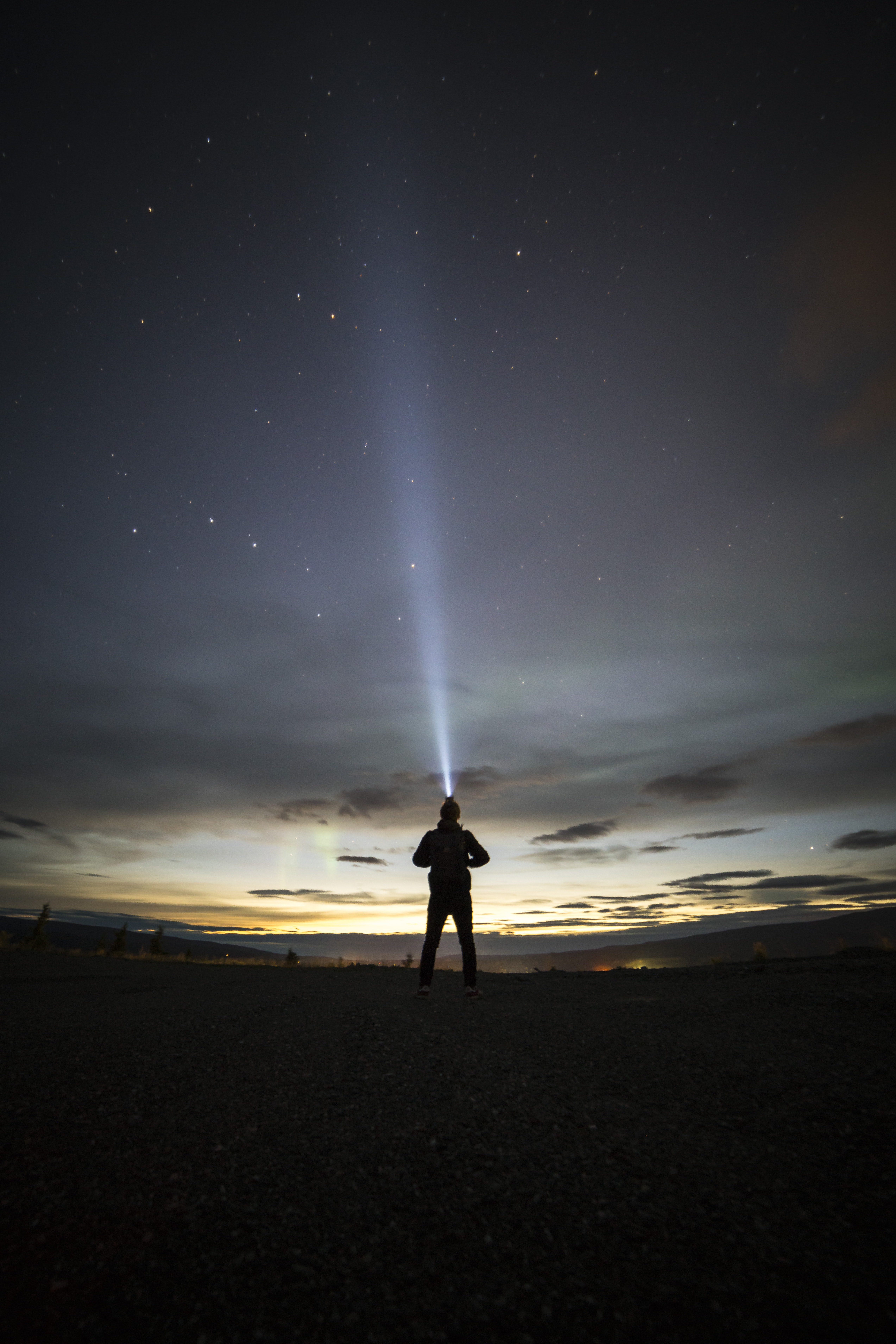 silhouette of person under starry sky during sunset