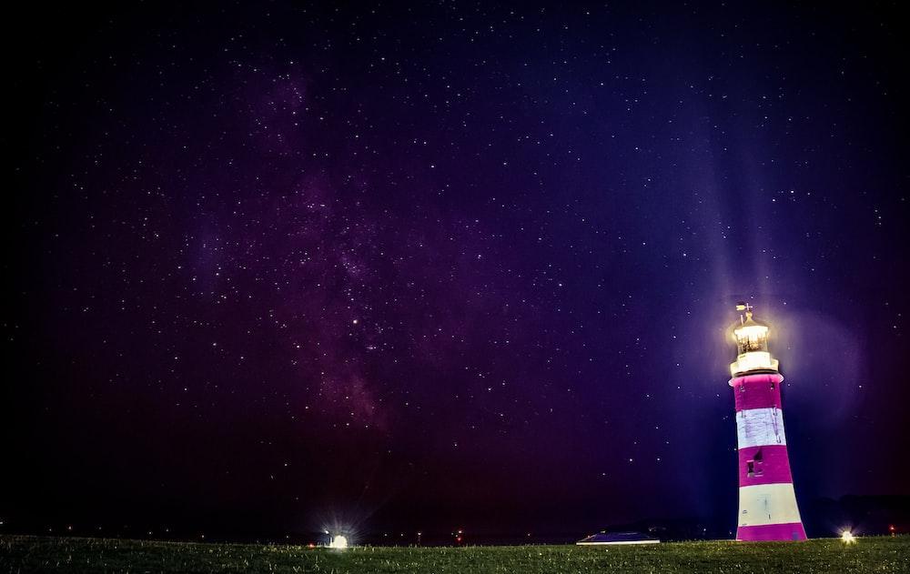 lighthouse turned on near green grass field