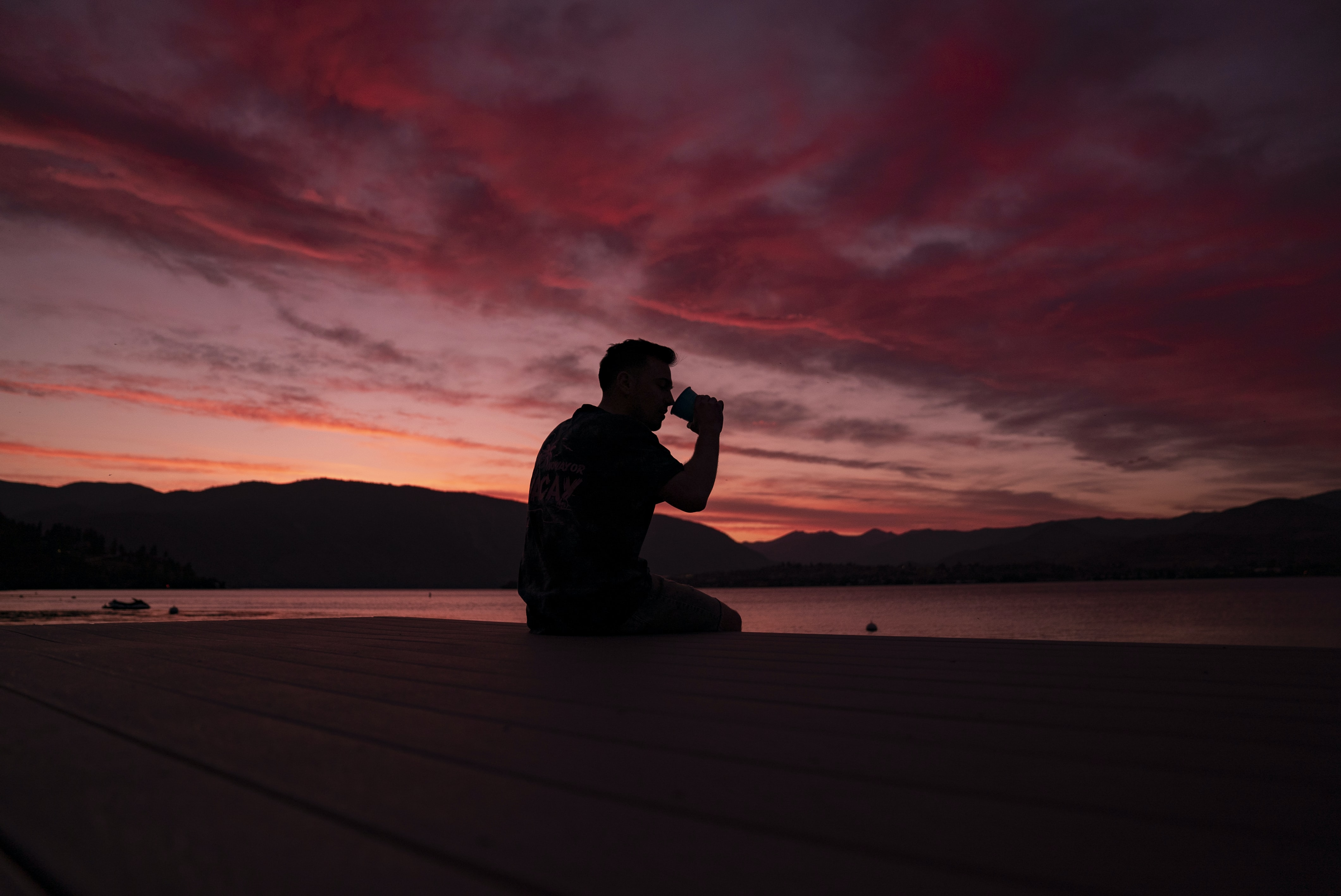 man sitting on dock during golden hour