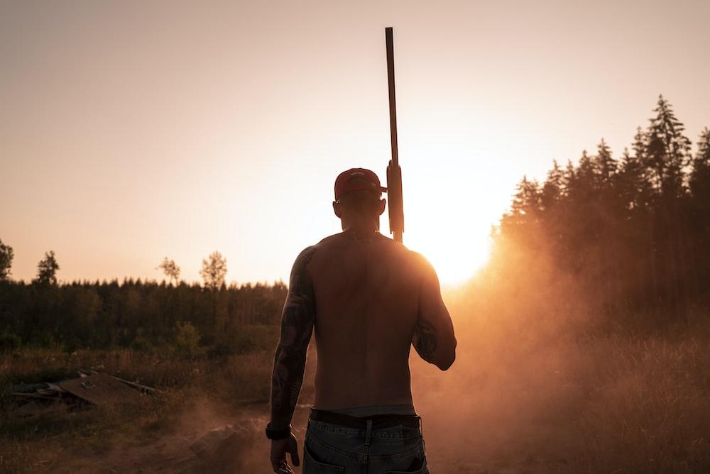 topless man holding shotgun