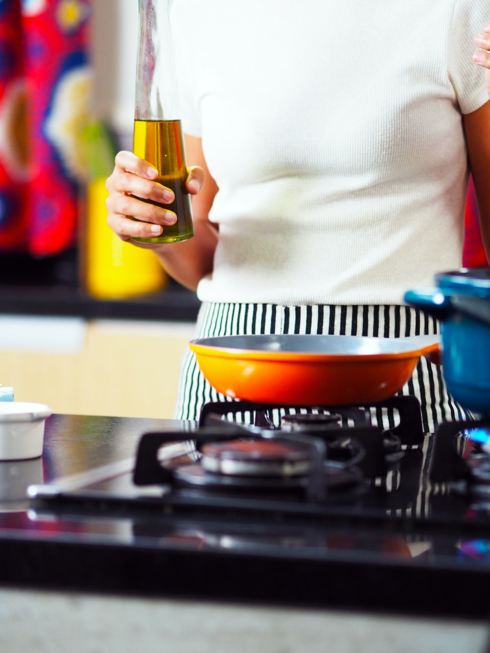 person holding bottle of oil at gas stove