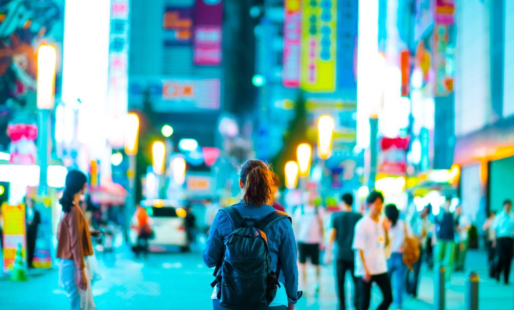 woman walks on street surrounded people