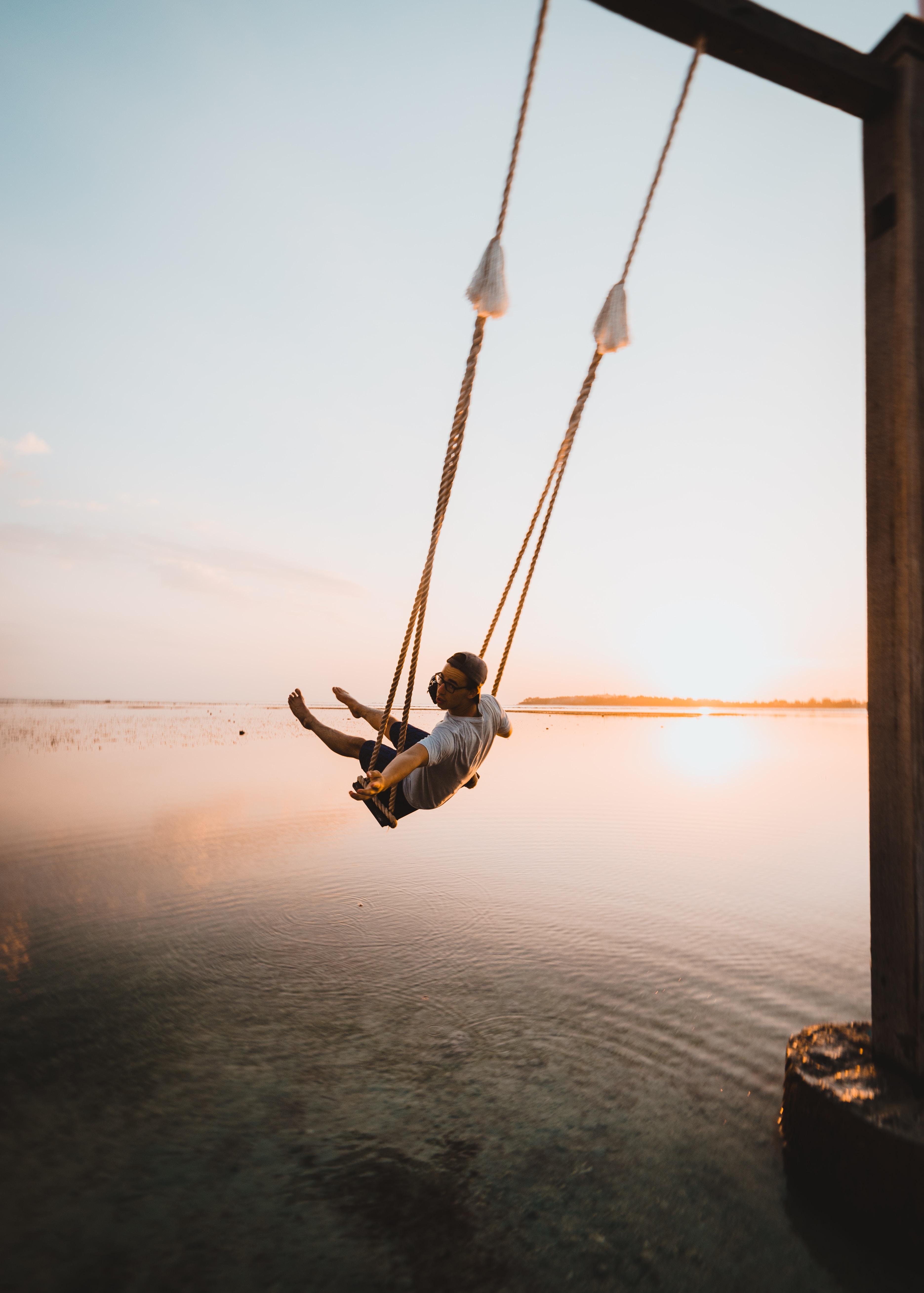 man on swing near body of water