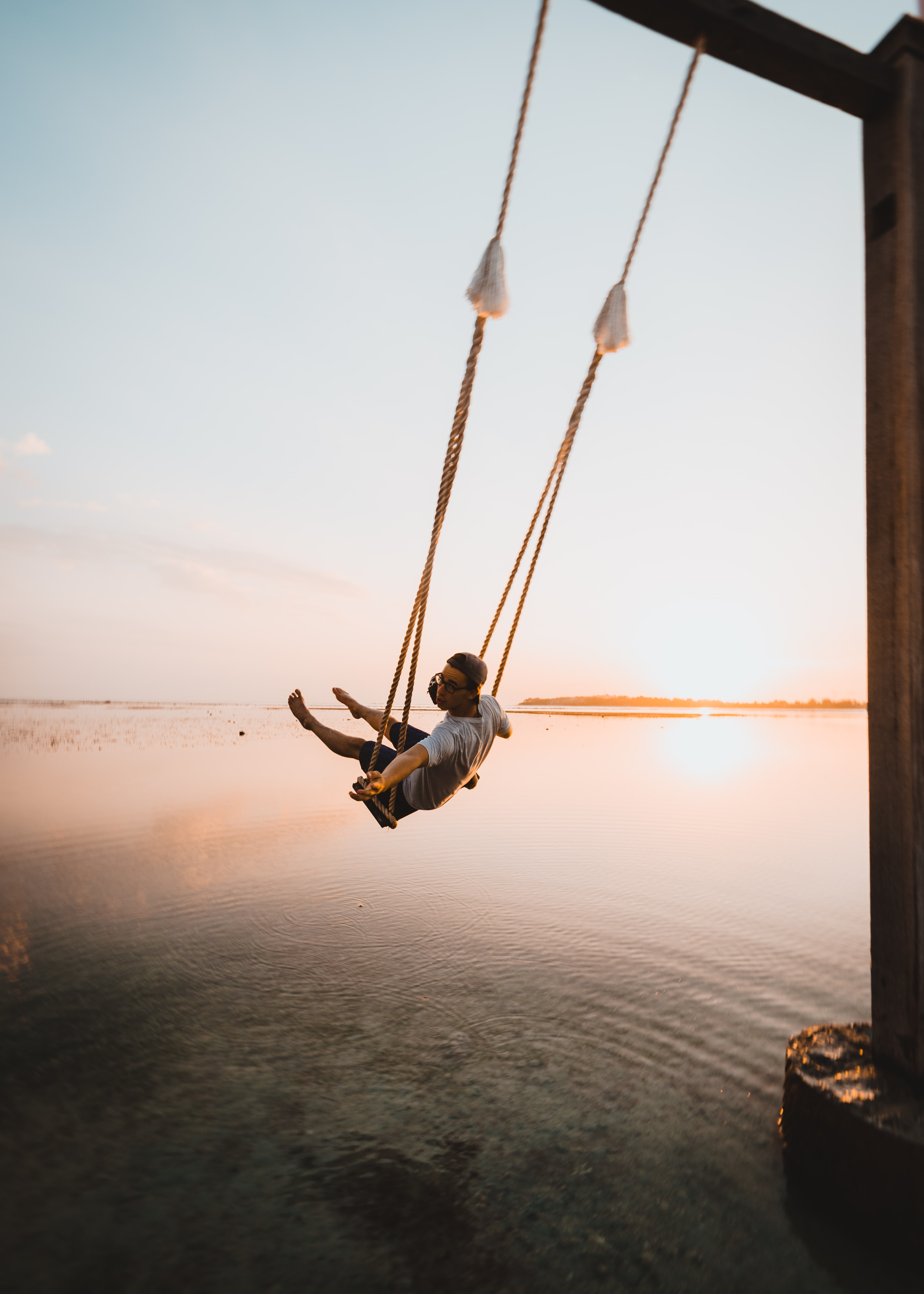 man on swing near body of water