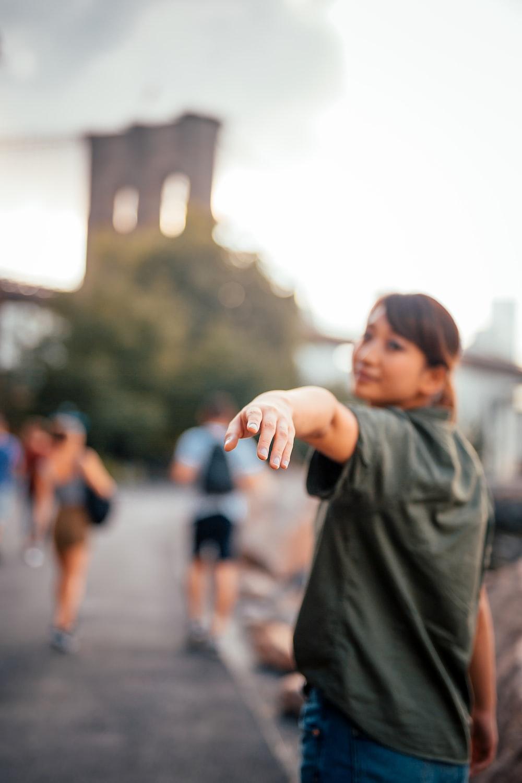 selective focus photograph of woman raising her hand