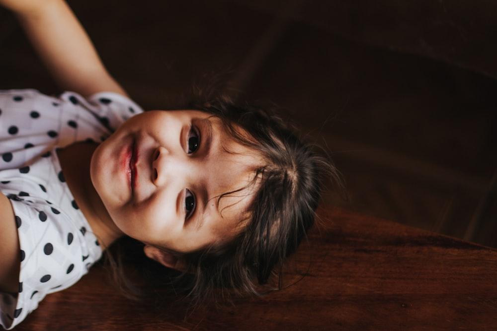 smiling girl gray and black polka-dot shirt near brown wooden wall at daytime