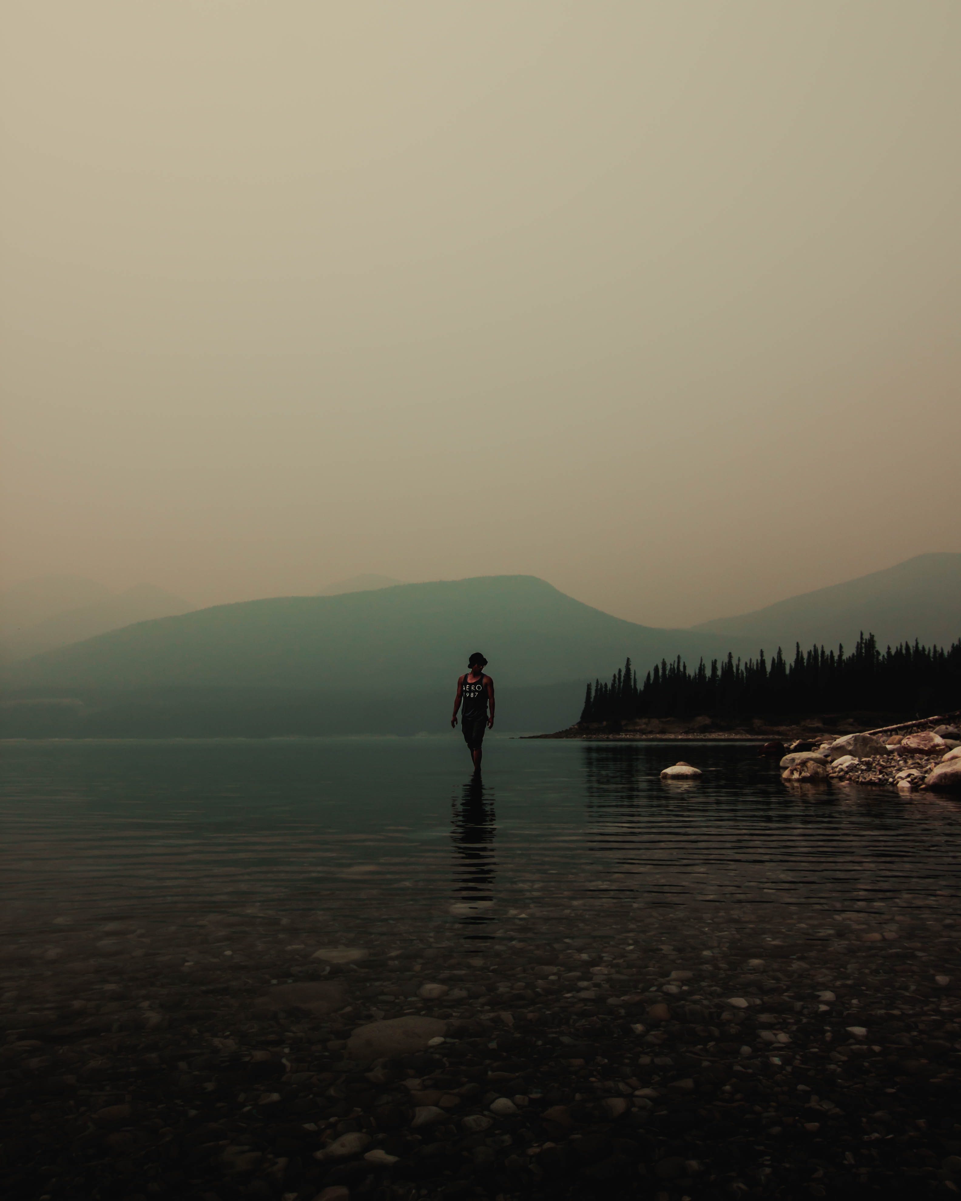 man standing on body of water and view of mountains
