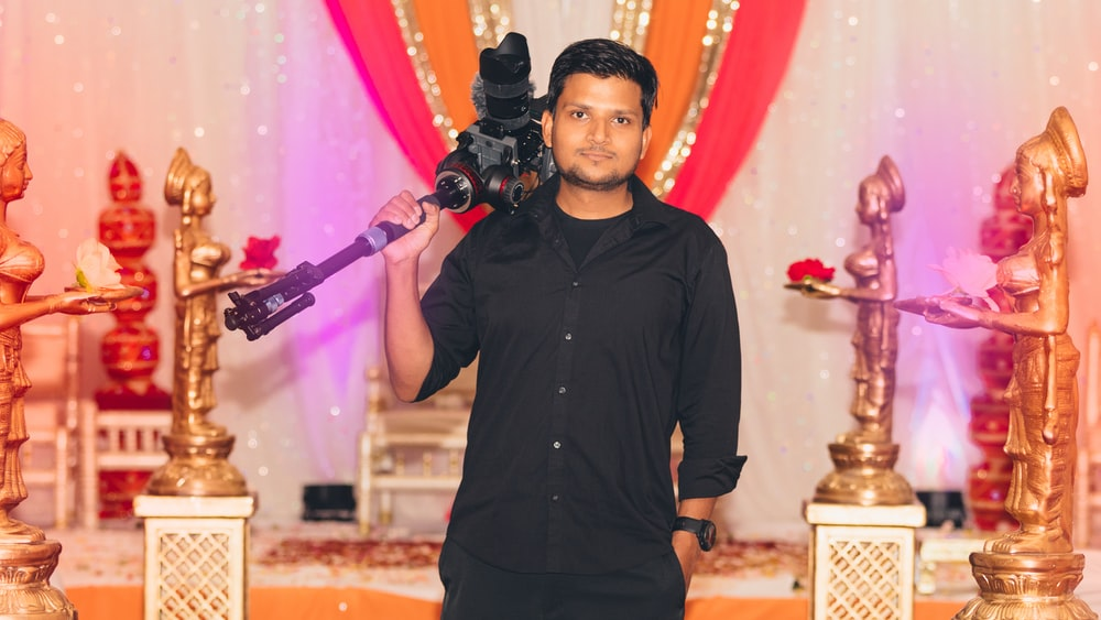 smiling standing man carrying camera