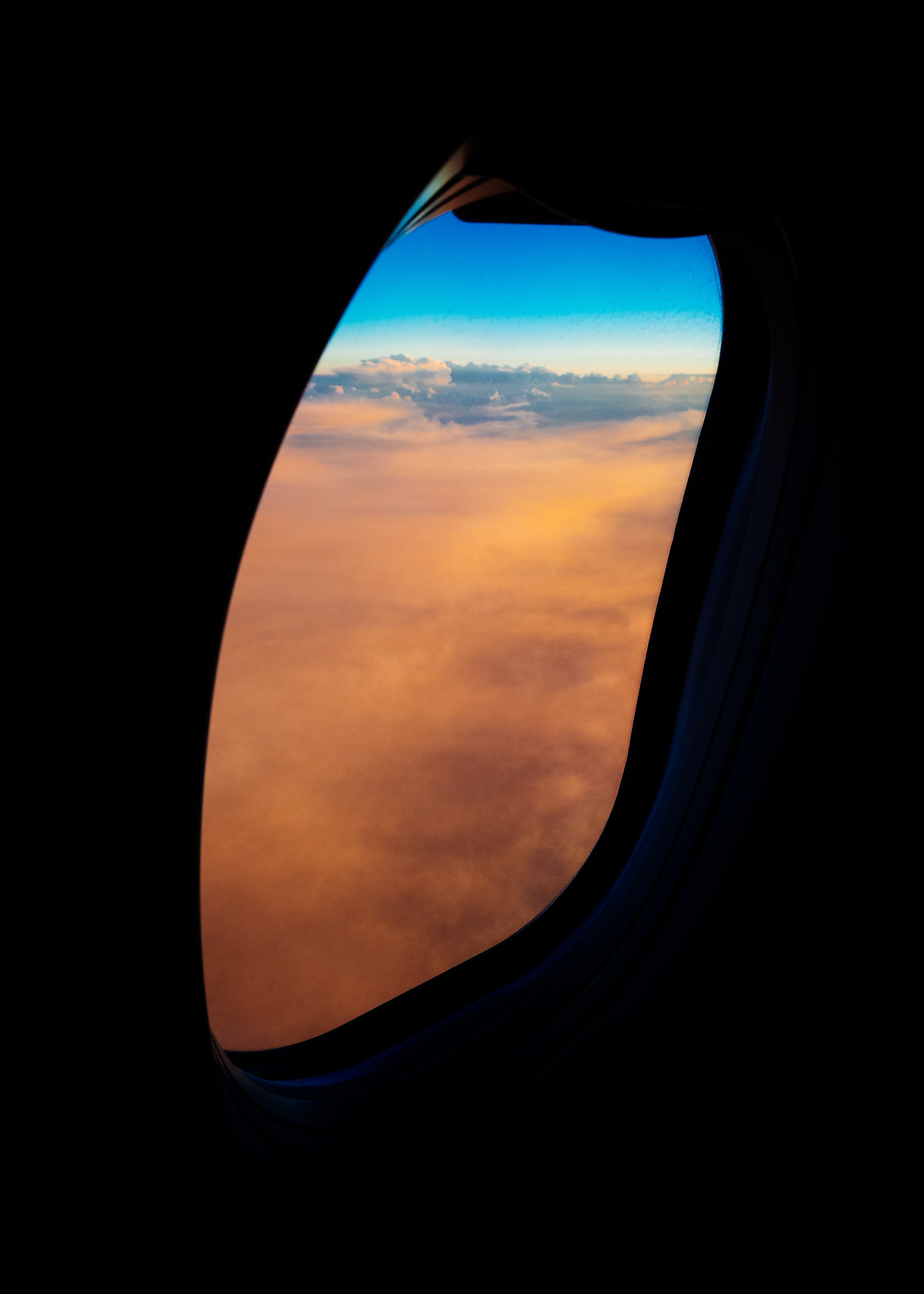 aircraft window overlooking orange clouds during daytime