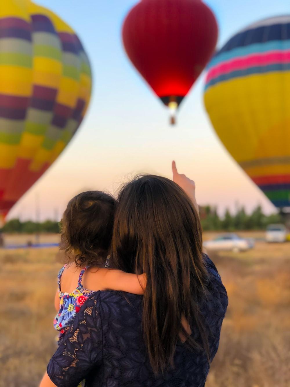 woman carrying toddler point at hot air balloon