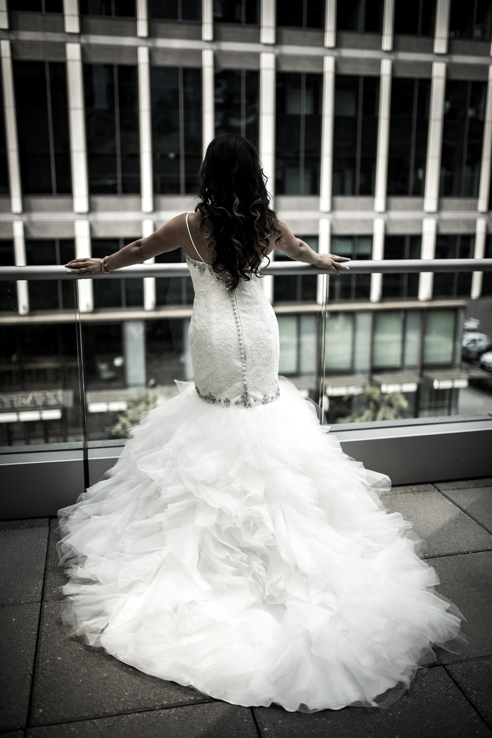 woman in white wedding dress standing in front balustrades