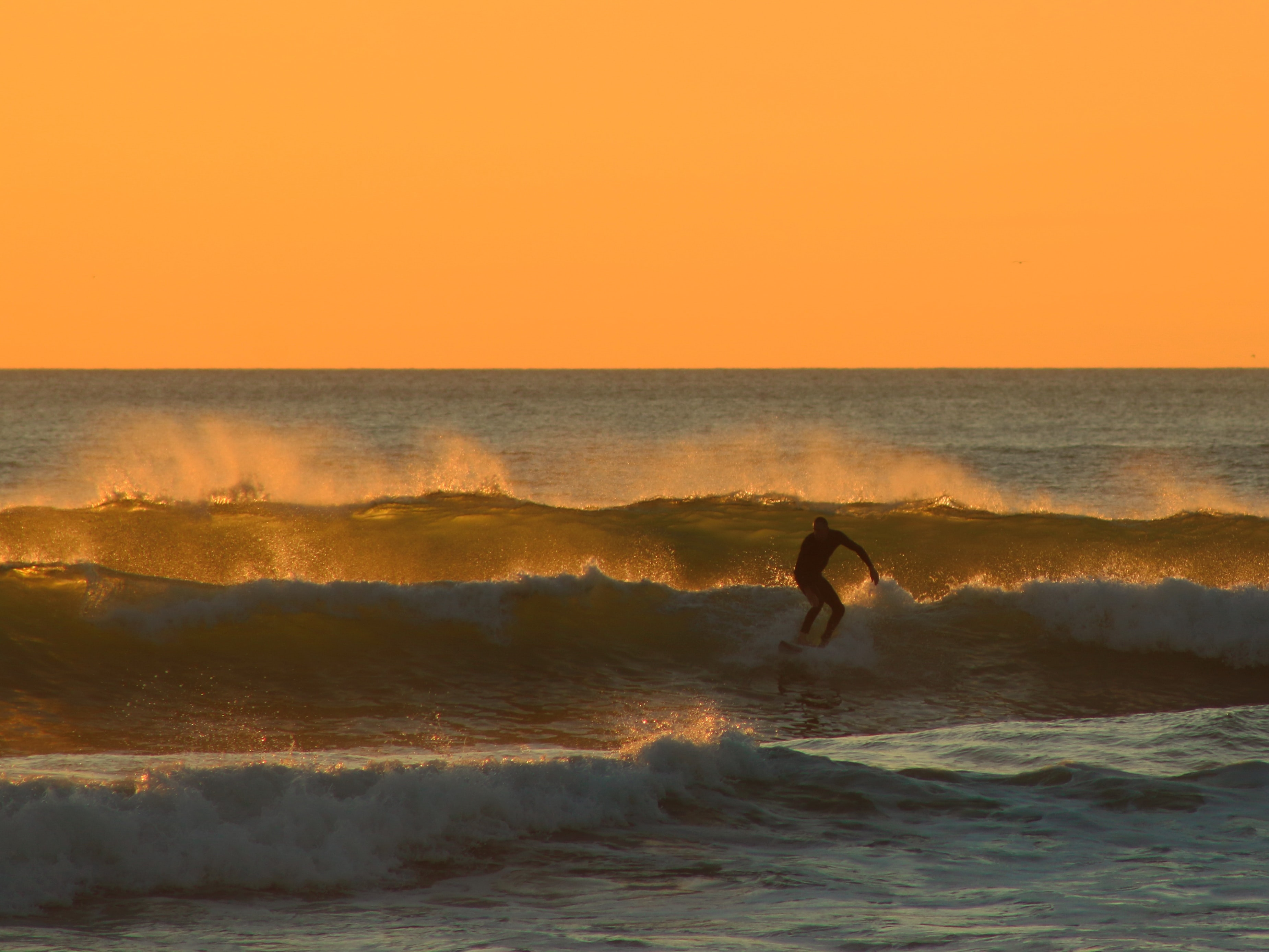 man surfing under yellow sky during daytime