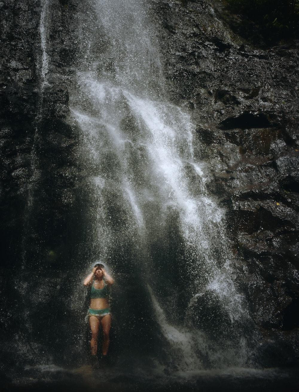 woman taking a bath in waterfalls