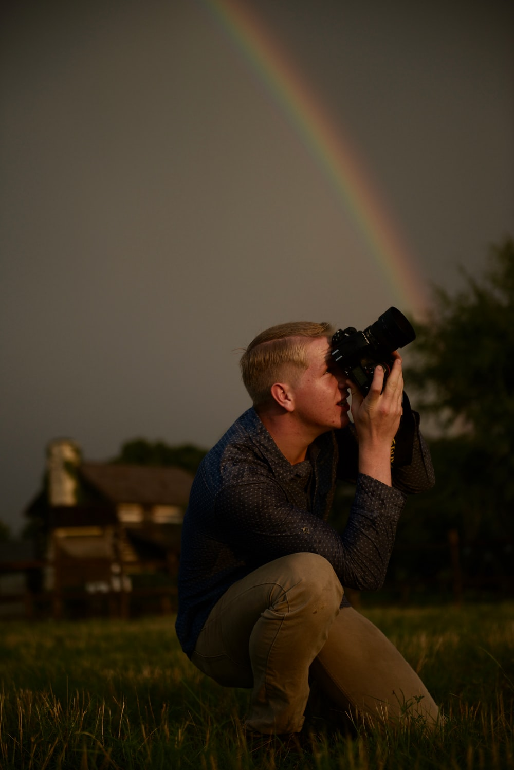 man kneeling while using DSLR camera