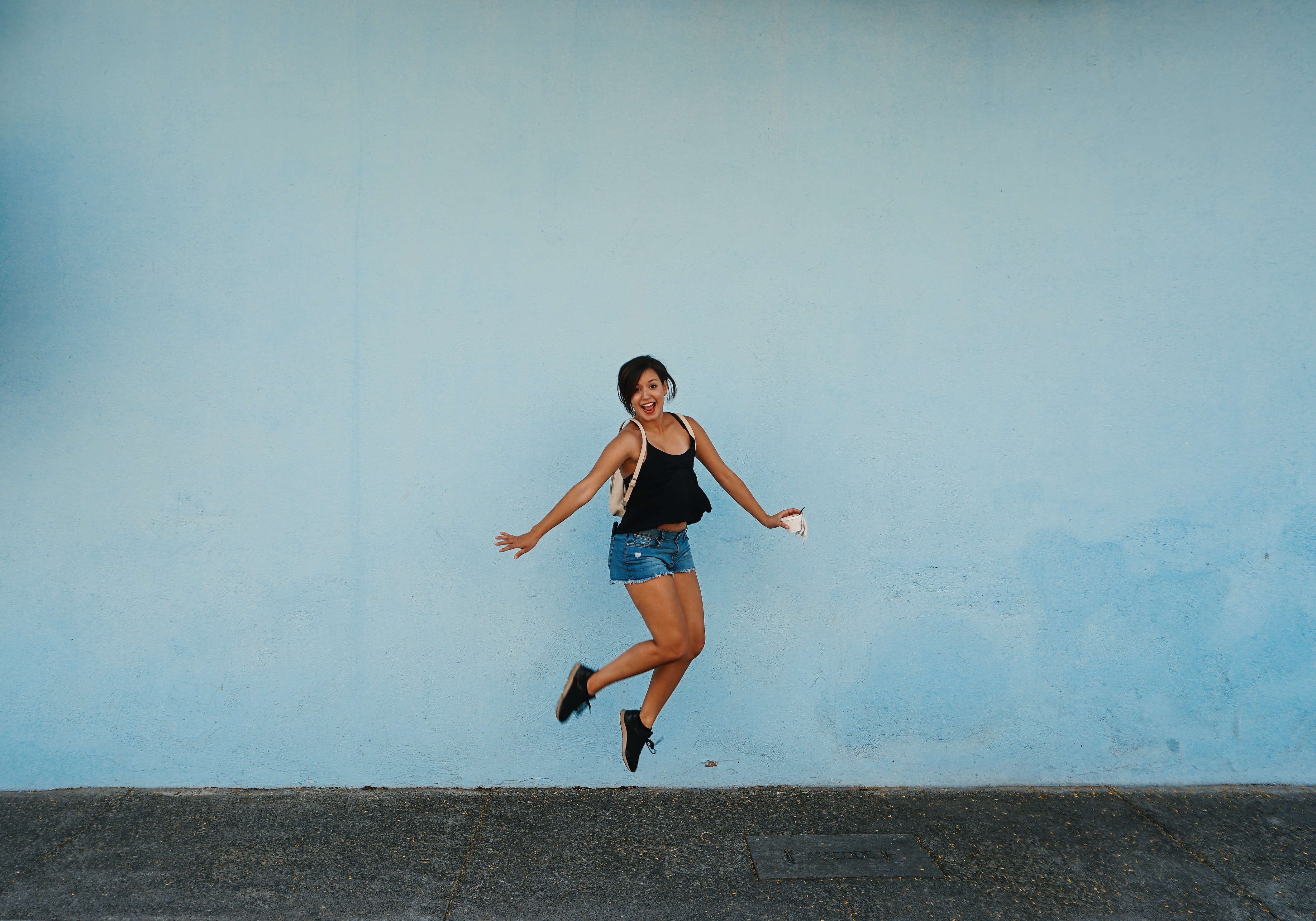 jumping woman on gray ground under white cloud blue skies