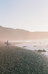 man holding white surfboard while walking on seashore in front of the sea