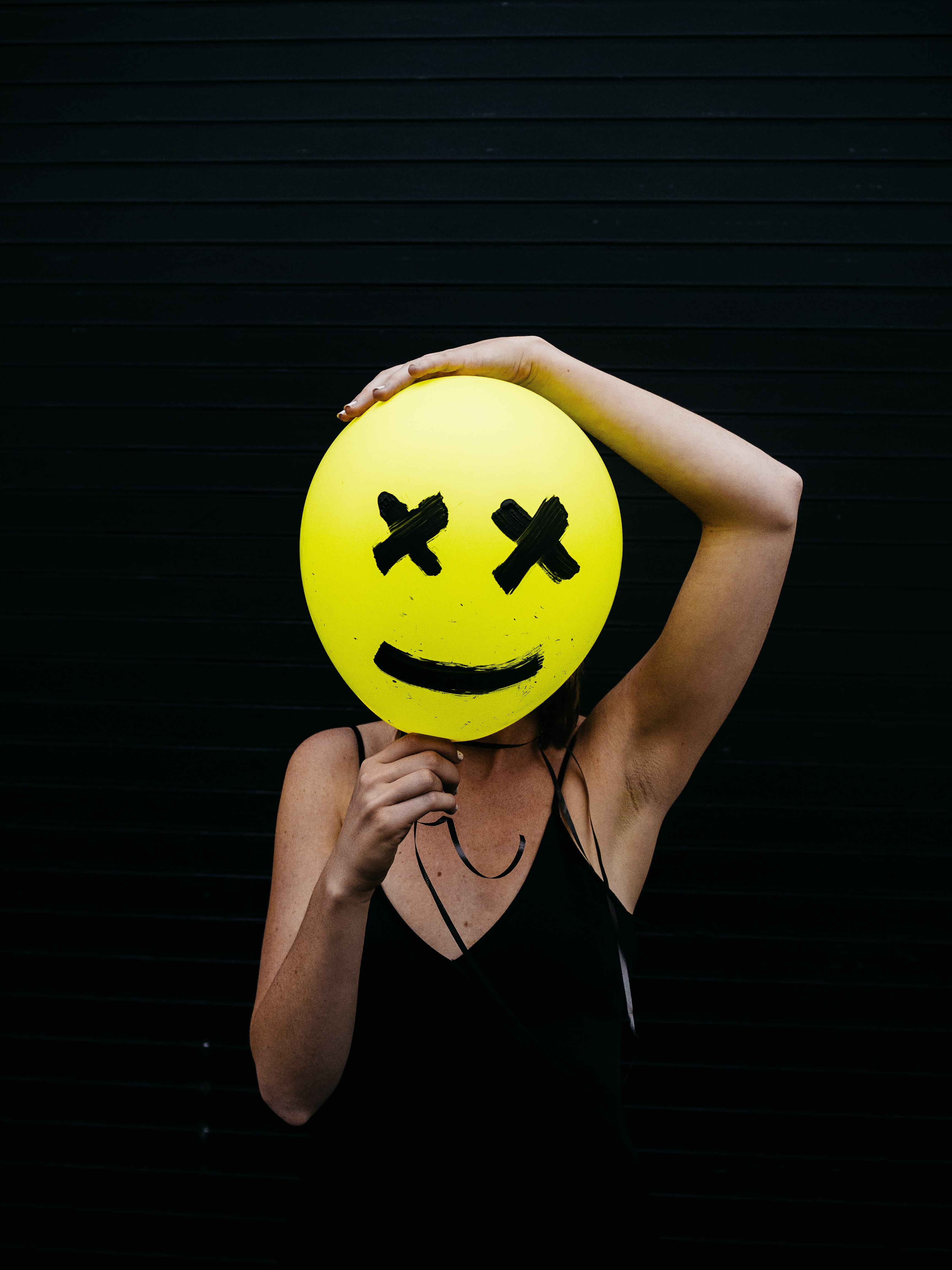 woman holding yellow and black balloon at daytime