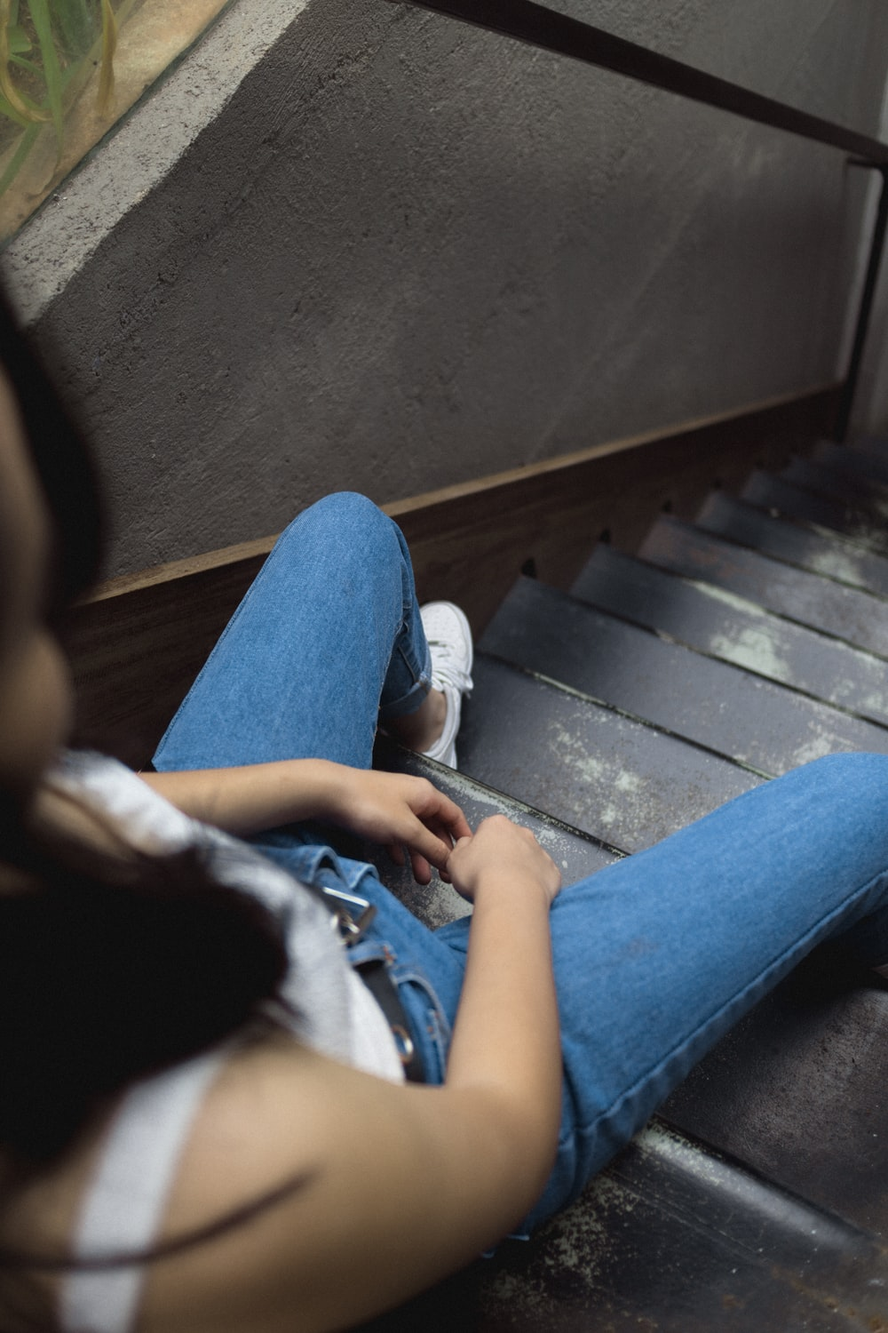 woman sitting on gray stairs