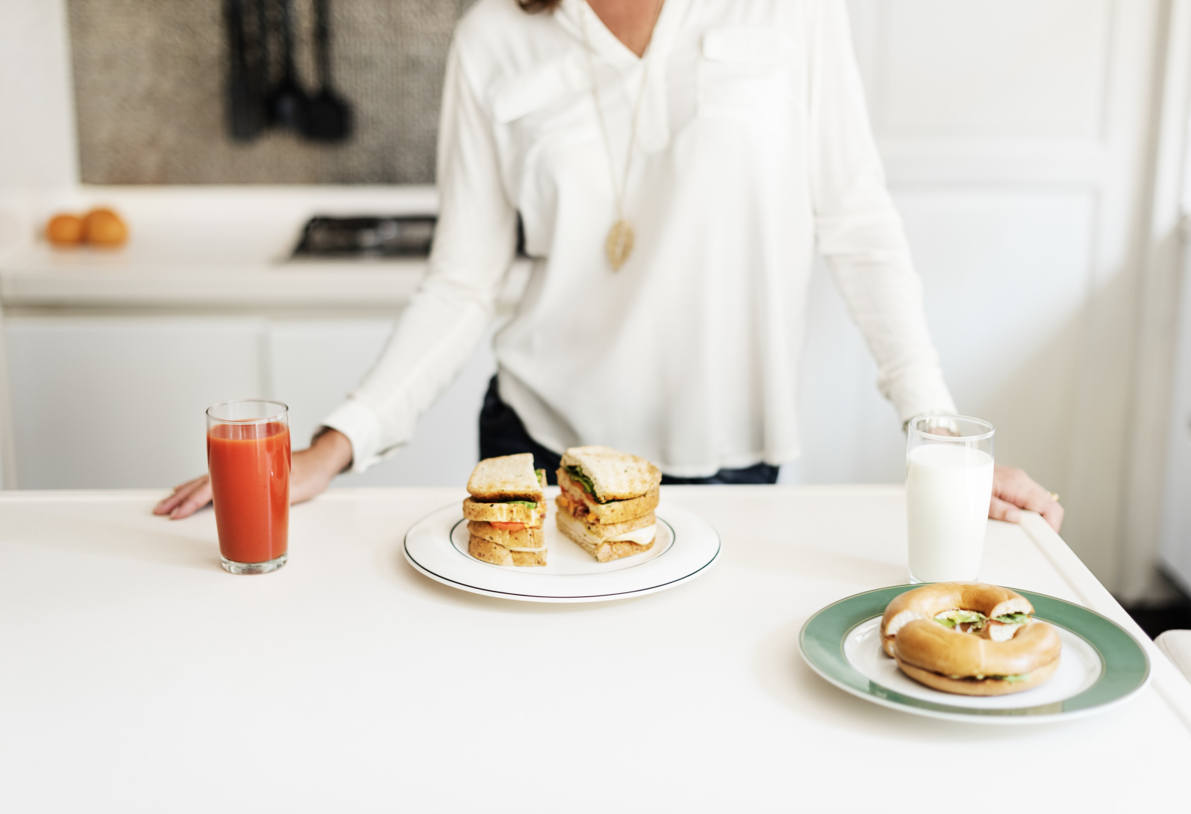woman standing in front of two plates of sandwiches