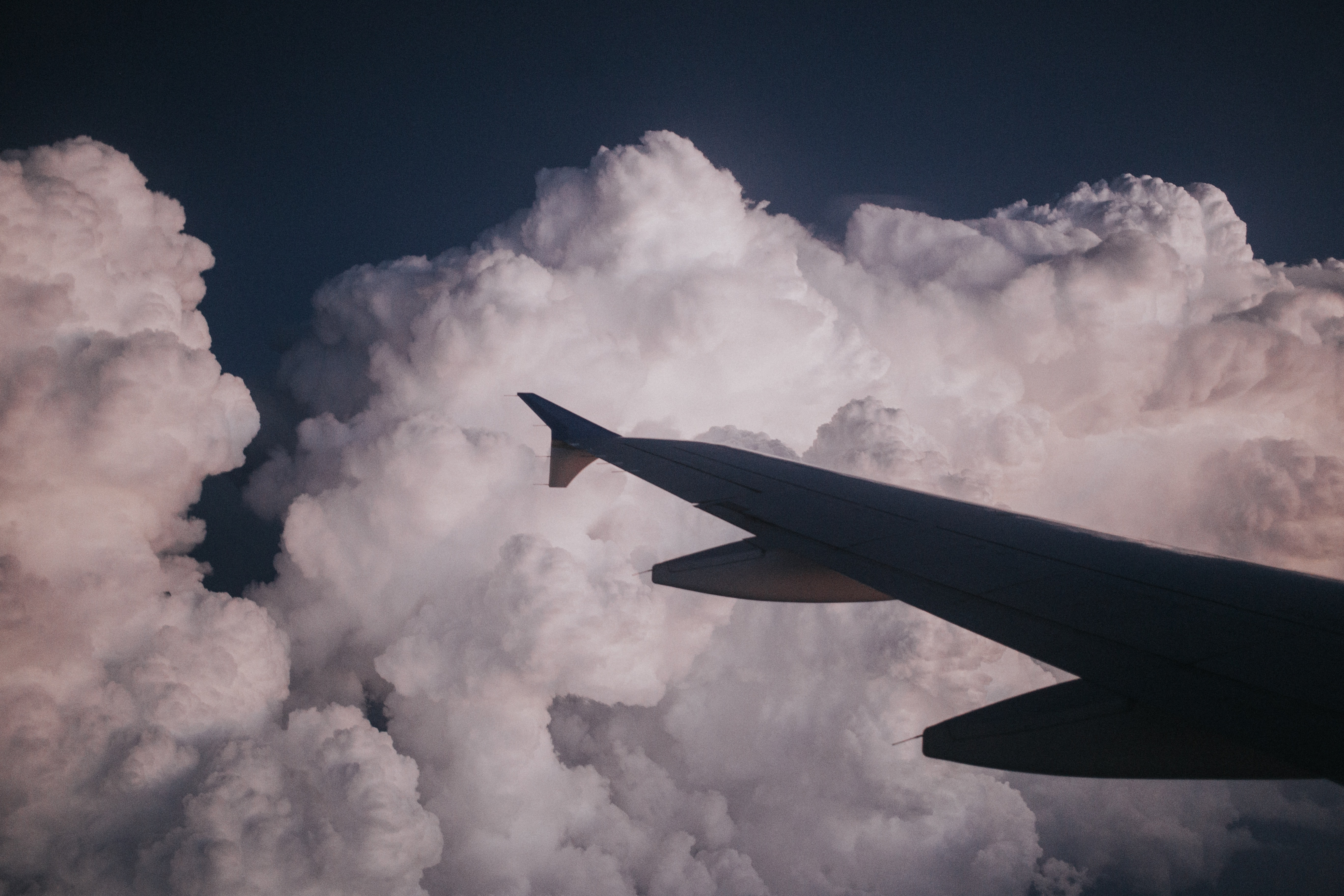 silhouette photography of plane's wing near cumulus clouds