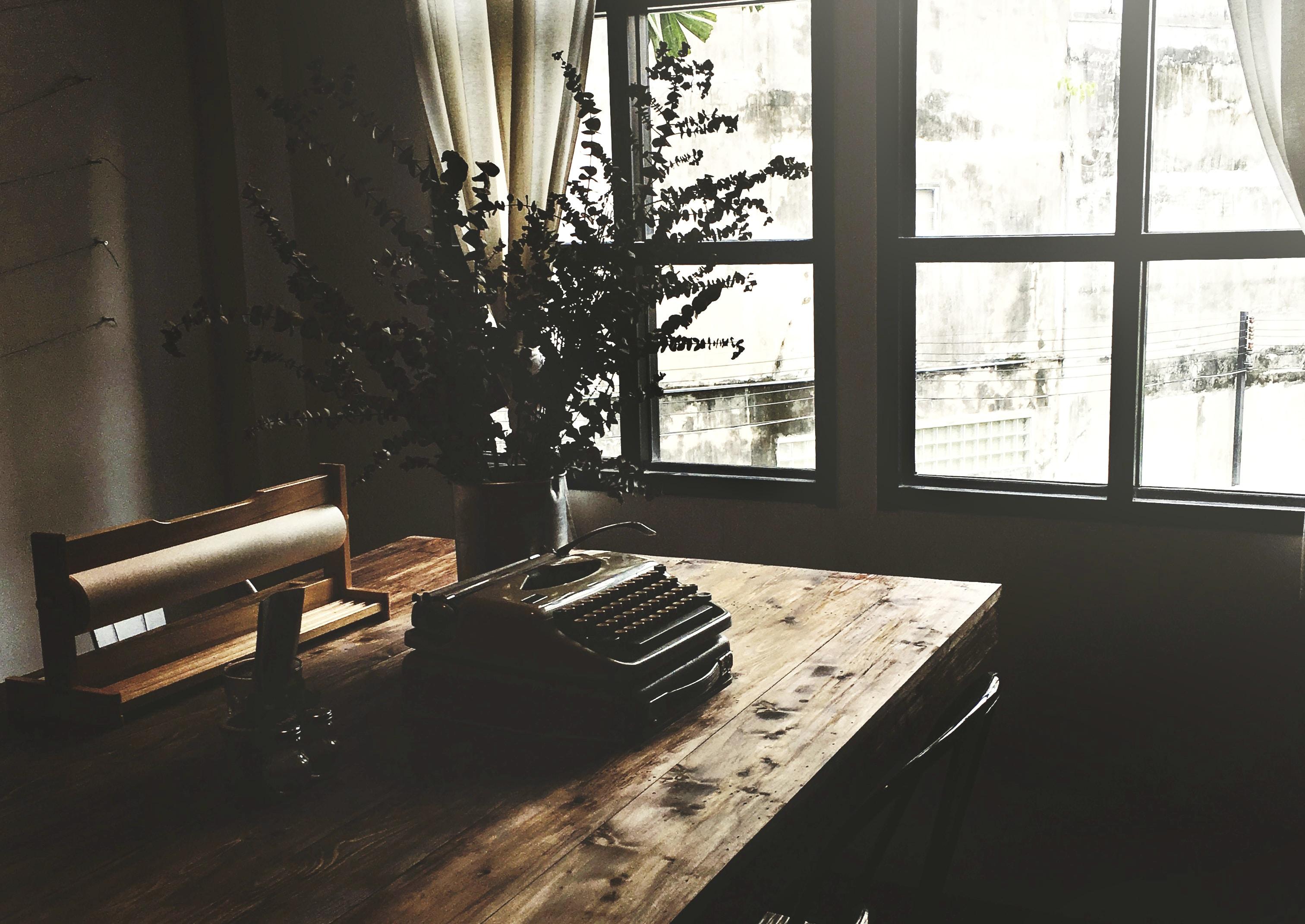 typewriter on wooden table near a window