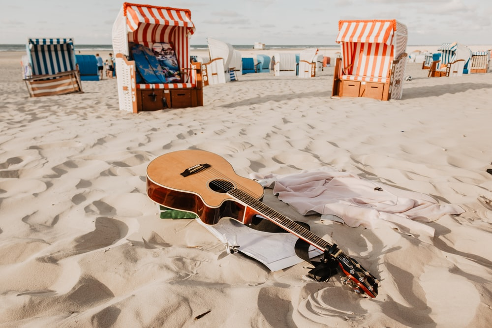 brown acoustic guitar on sand during day time