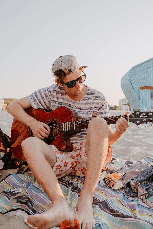 man wearing gray tee shirt holding red guitar