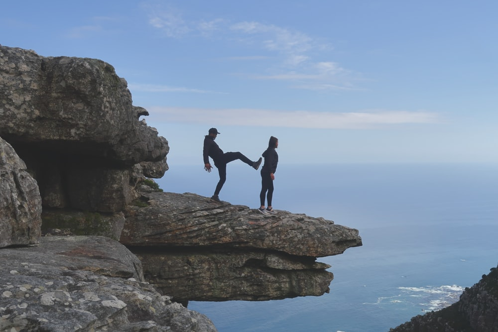 man about to kick woman standing on cliff