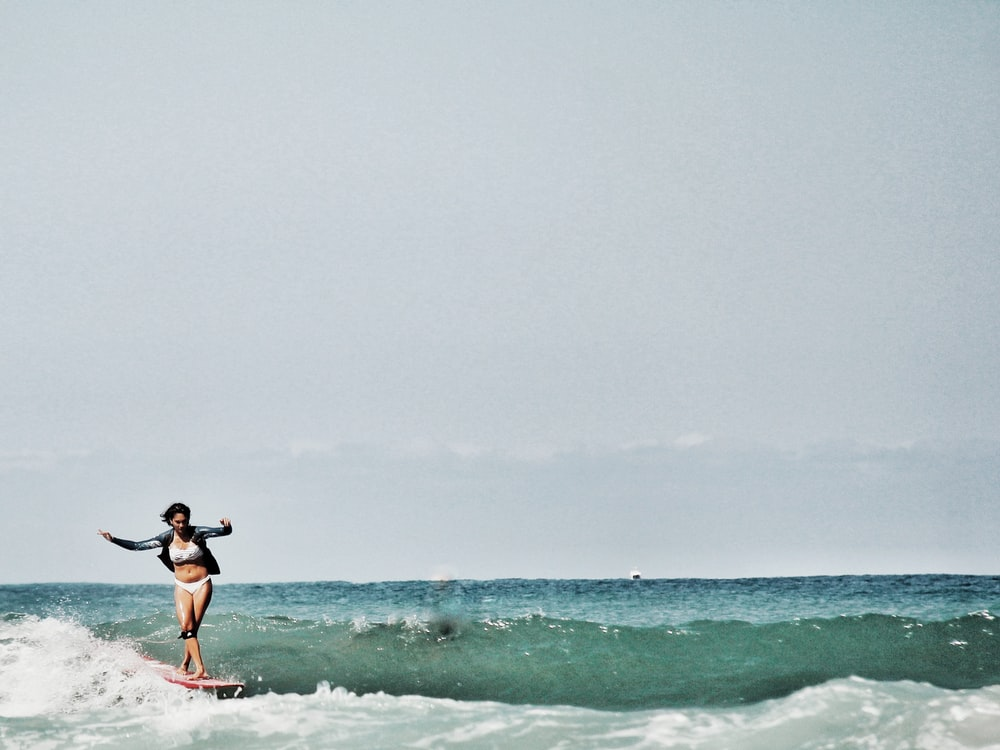 woman surfing on sea during daytime
