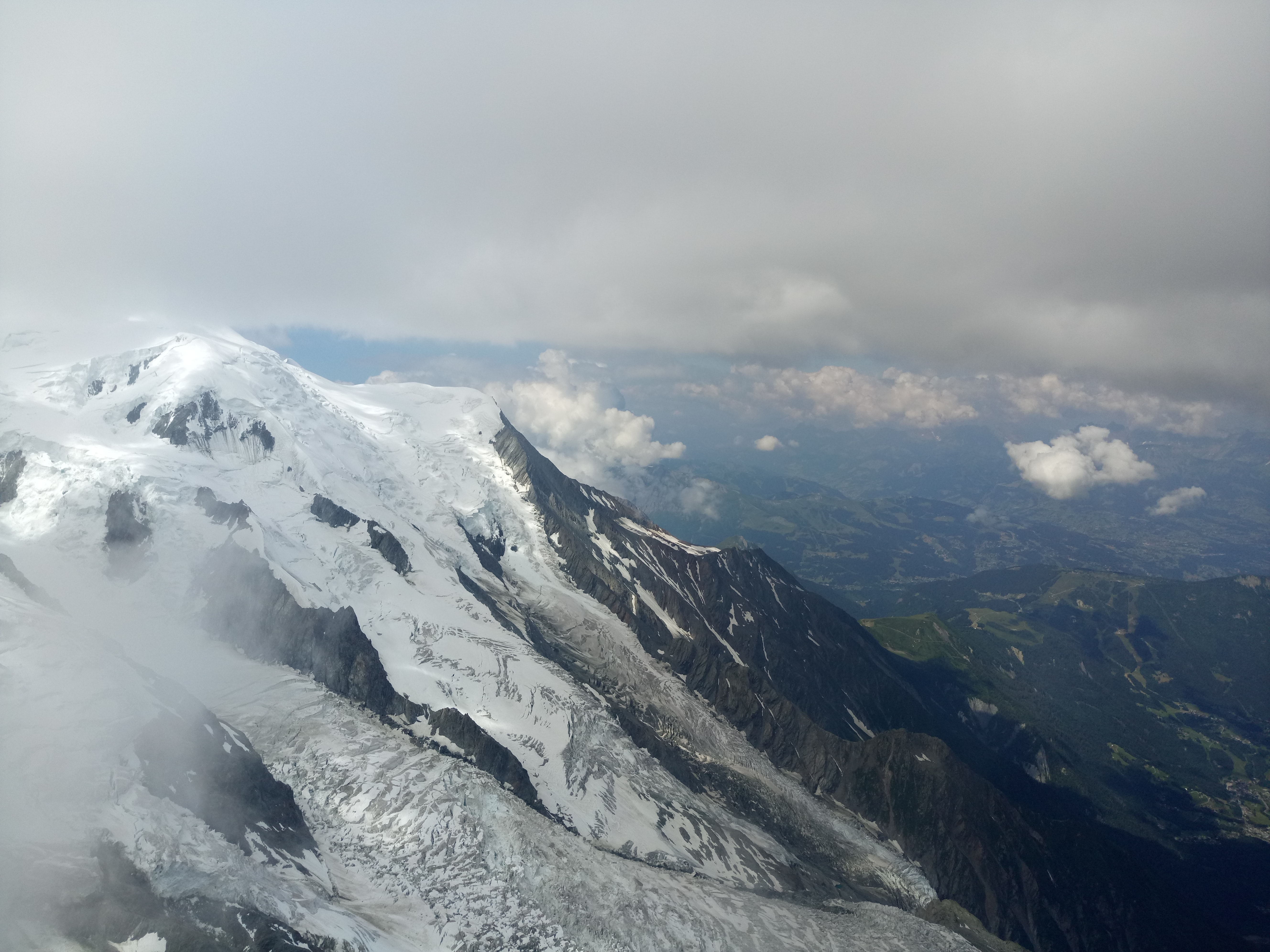 snow capped mountain under white clouds at daytime